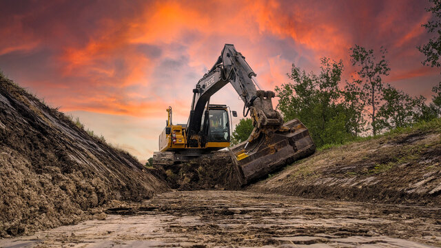 John Deere 210g excavator with a tilt bucket digging a new ditch along the side of the road.