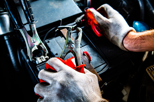 Male hands attaching clips to a car battery, close-up.