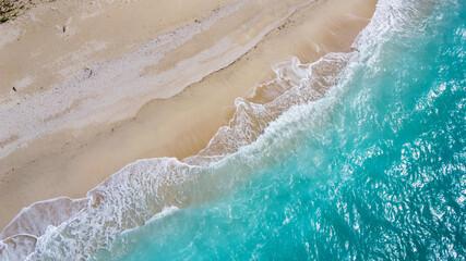 美しいアクアブルーの海と砂浜に白波が立つドローン俯瞰写真