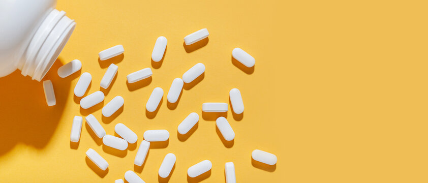 White pills are poured from a jar on a yellow background. Food supplement, multivitamins, medications