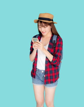 Beautiful young asian woman touch smart mobile phone in vacation isolated on blue background, asia girl talking or chat message on smartphone in travel summer trip, journey or education concept.
