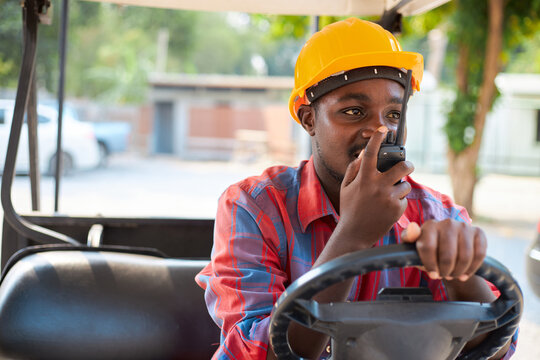Black engineer is talking on the walkie-talkie while sitting in a forklift.