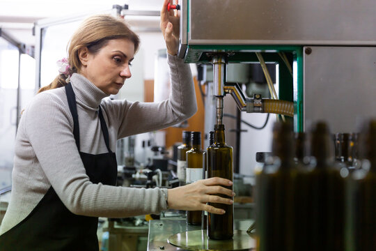 Experienced woman working on bottling line of artisanal olive producing oil factory..