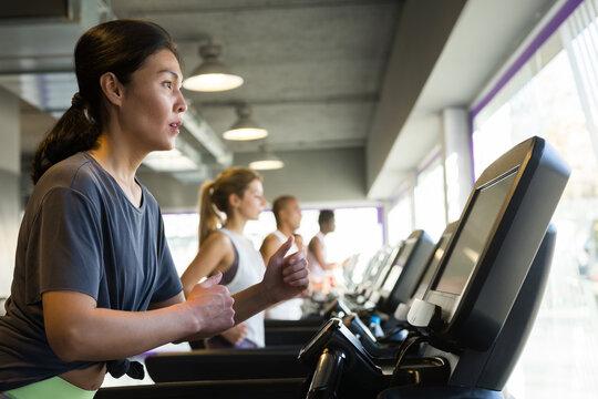 Athletic girls running on treadmill in fitness club