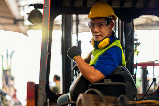 Engineer or technician Concept. A male employee driving a forklift and showing thumb up in factory.
