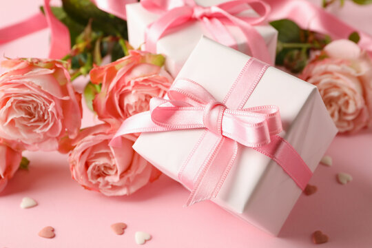 Roses and gift boxes on pink background, close up