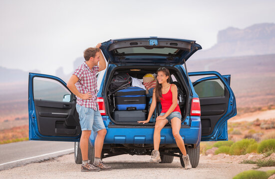 Car travel road trip couple of happy man and Asian woman packing luggages in the trunk of SUV driving on adventure road in the USA. Summer vacation destination friends traveling. Outdoor lifestyle.