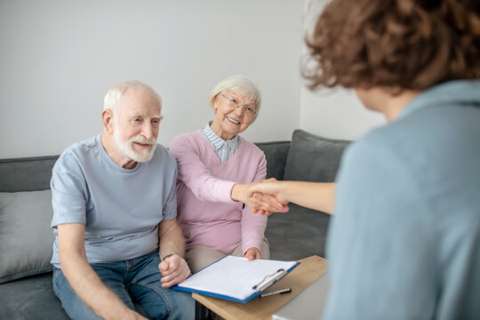 Senior couple meeting insurance company agent and looking involved