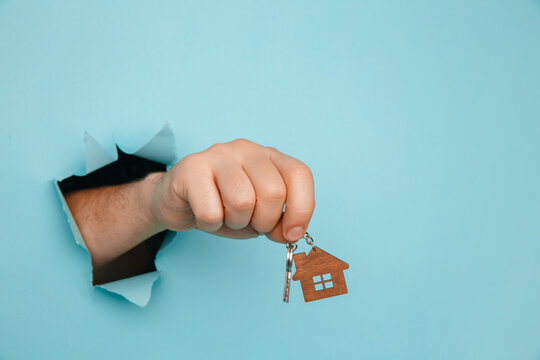 Man's hand with house keys through a hole in blue paper. House sale and rent concept.