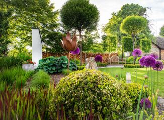 Fototapeta Piękne kule bukszpanu wśród ozdobnych traw w zadbanym zielonym ogrodzie
