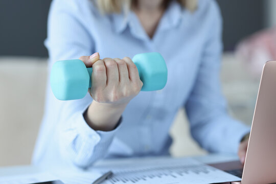 Woman sits on laptop and holds blue dumbbell in her hand