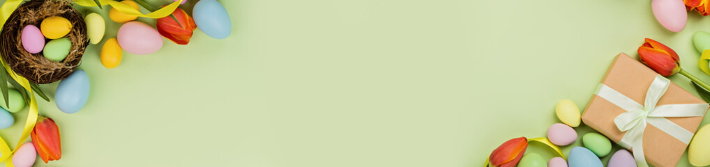 Stylish background with colorful easter eggs pastel colors isolated on green background. Horizontal long banner for web design. Flat lay, top view, mockup, overhead, template