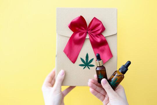 Female hands are holding gift box and bottle of marijuana