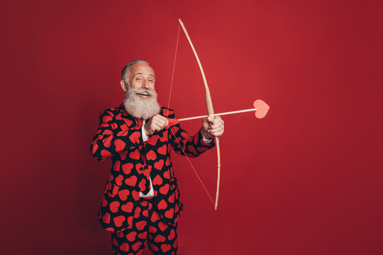 Photo of positive retired cherub man hold bow arrow prepare shoot wear heart print tux isolated red background