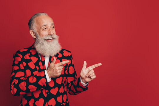 Photo of bearded promoter man fingers indicate look empty space wear heart print tuxedo isolated red background