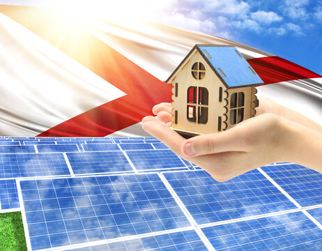 The photo with solar panels and a woman's palm holding a toy house shows the flag State of Alabama in the sun.