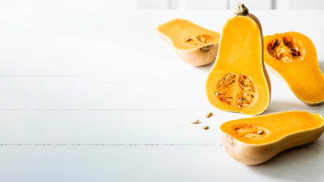 Butternut squash halves on white wooden table