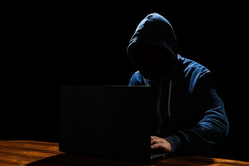 Fototapeta A Hacker with laptop sits at a table and abstract binary code. Business life threat virtual programs.