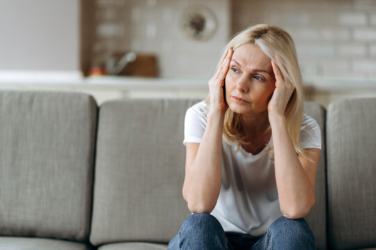 Sad caucasian senior woman wearing casual clothes sits on couch at home alone feels unhappy because of headache, stress, illness or bad news, she needs rest and sleep