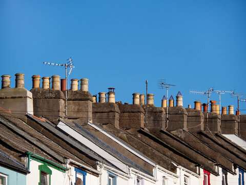 Small town house rooftops, England, UK. Aerials and blue sky.