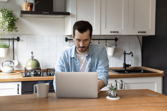Working spirit. Concentrated millennial guy engaged in telework from home typing email on modern laptop keyboard. Male remote employee consult customer using messenger app or search data in internet