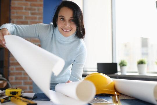 Smiling female architect holding white whatman paper