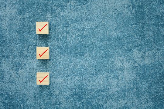 check mark on wooden cubes with blue background, checklist concept