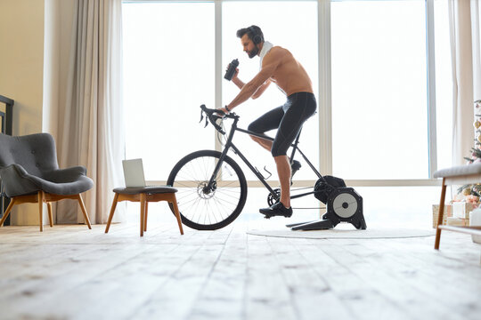 Shirtless young man riding stationery bike and drinking water