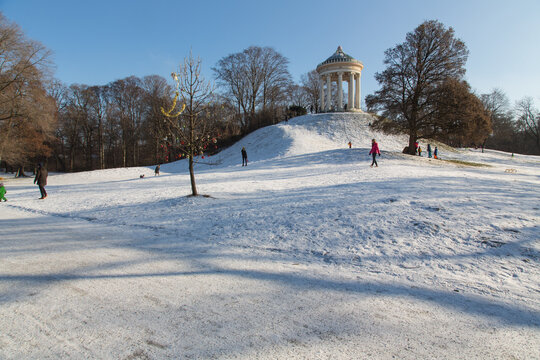 Winter Idylle im Englischen Garten, München: Der Rundtempel Monopteros mit seinem bekannten Rodel und Schlittenhang für Kinder