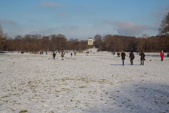Winter Idylle im Englischen Garten, München: Blick auf den Rundtempel Monopteros beim Spaziergang im verschneiten Stadtpark