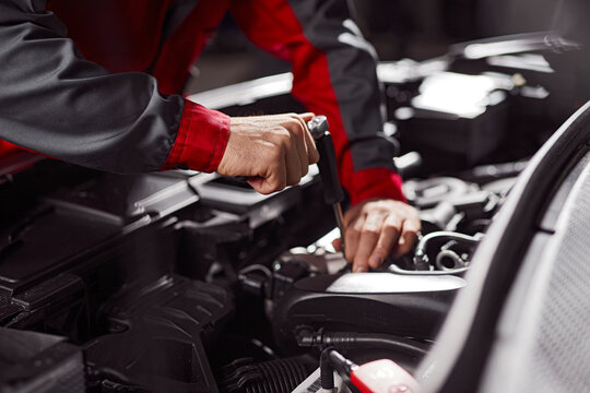 Mechanic repairing automobile engine in workshop