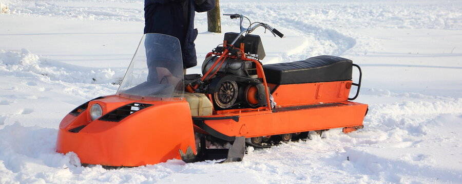 A driver near orange old broken Russian utility single ski snowmobile without cover close up - steering, engine handle and fuel tank on white snow at winter day
