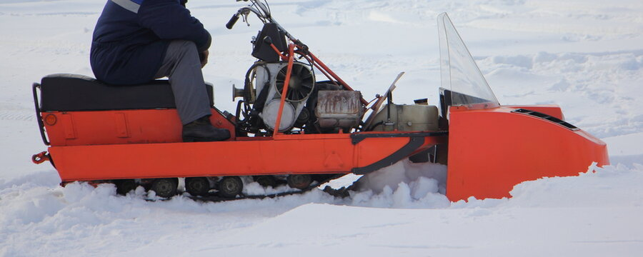 A Polar explorer driver sitting on old broken Russian utility snowmobile without cap on white snow at winter day