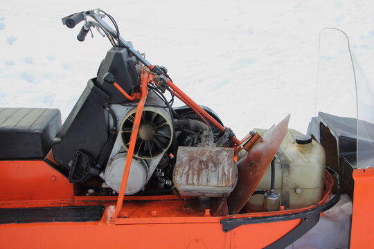 Old vintage Russian utility snowmobile without cover closeup - steering, air cooled engine with emergency motor start handle and fuel tank