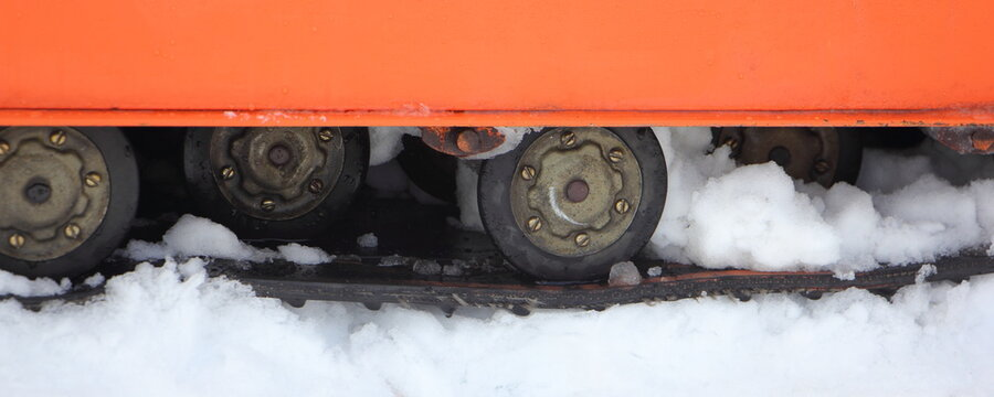 Old Soviet utility snowmobile roller crawler drive gear with snow close up