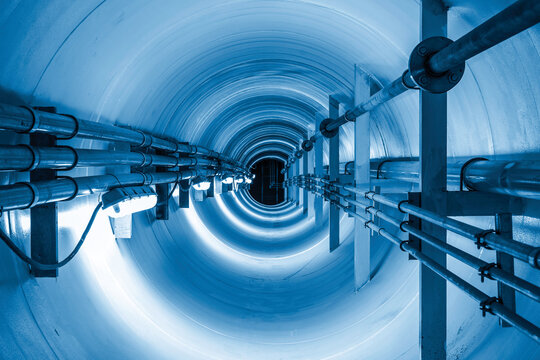 Confined space inside underground tunnel. Construction from engineering technology for infrastructure i.e. power line or cable, steel pipe in perspective view. To transport water, gas and electricity.