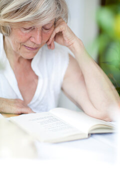 Seniorin sitzt hinter einem Fenster und liest