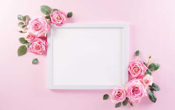 Happy women's day concept, pink roses with white picture frame on pastel background