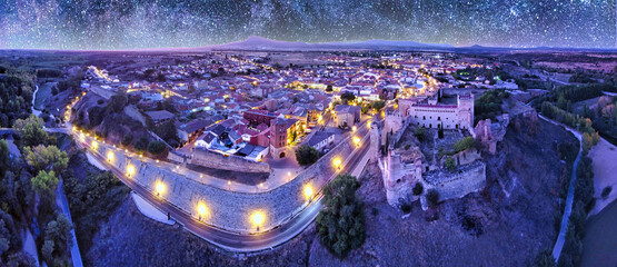 Wide angle lens view of a small illuminated village under a starry night sky