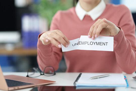 Woman tears inscription unemployment in office closeup