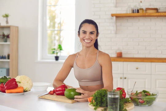 Portrait of happy female cooking healthy vegan food. Fit young woman in sportswear looking at camera and smiling, sitting at kitchen table with cutting board and lots of vegetables for vegetarian meal