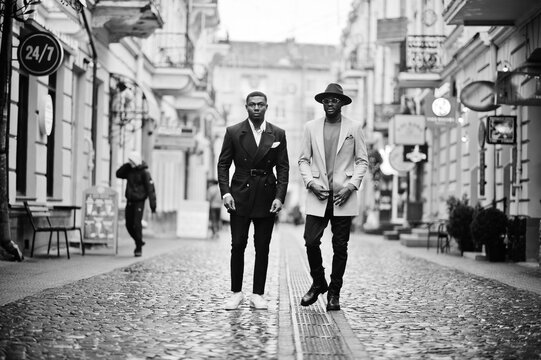 Two fashion black men walking on street. Fashionable portrait of african american male models. Wear suit, coat and hat.