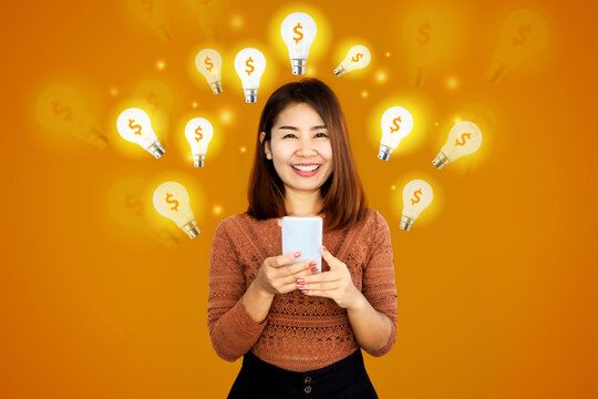 smiling Asian woman holding mobile phone with lightbulb icon and dollar sign,  idea for make money online ,e-business concept