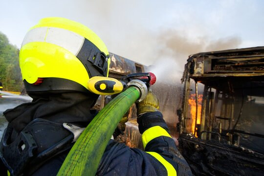 Firefighter in a helmet extinguishes a massive fire of several public transport buses using water from a hose with flames and smoke