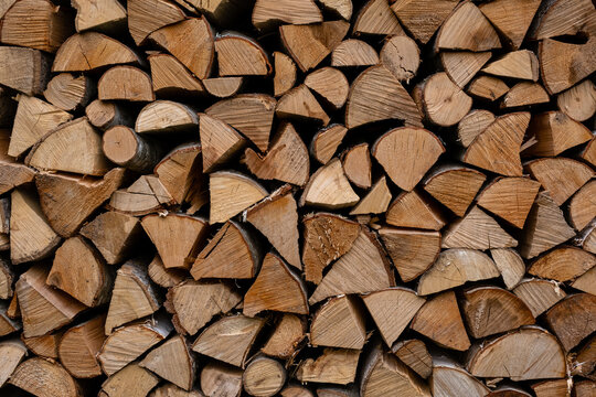 foreground of a pile of split firewood with ends of firewood of different shapes