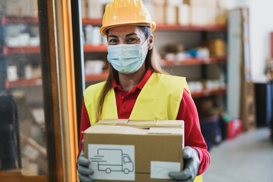 Mature latin woman at work inside warehouse holding delivery box while wearing protective face mask for coronavirus