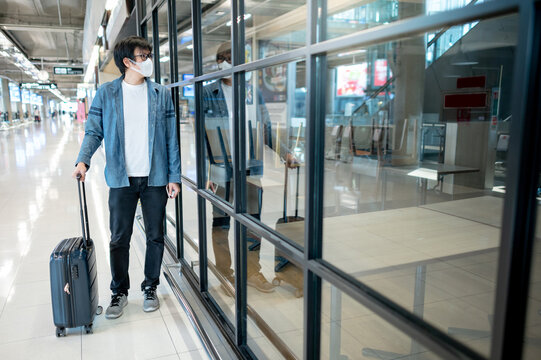 Asian man tourist wearing face mask carrying suitcase luggage looking at closed restaurant in airport terminal. Coronavirus (COVID-19) pandemic prevention. Health awareness and social distancing
