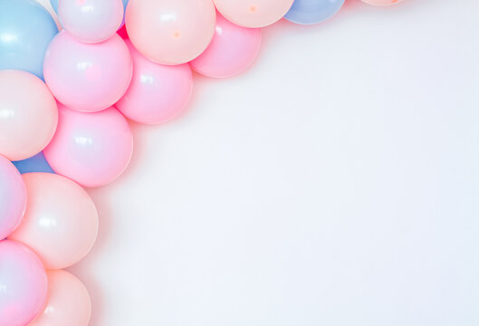 Colorful and joyful set of birthday balloons on a white wall.
