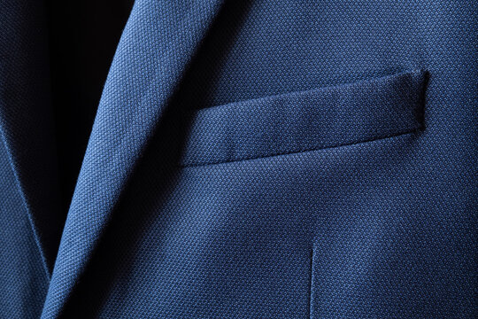 High resolution with details and quality shot of formal dark blue wool suit fabric texture. with front pocket decoration under light and shadow ambient. Ideal for background or wallpaper.
