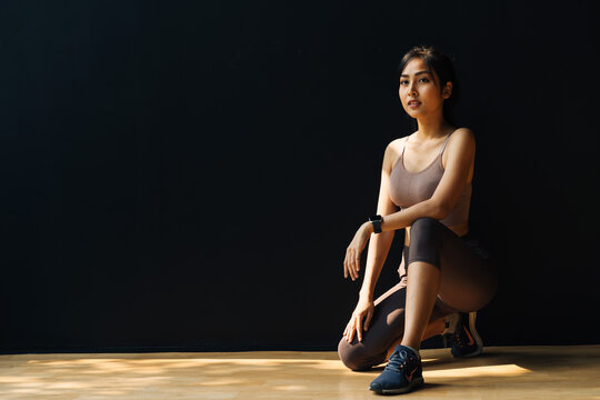 Focused young Asian sportswoman relaxing and getting ready for workout while crouching in studio on black background - full body length